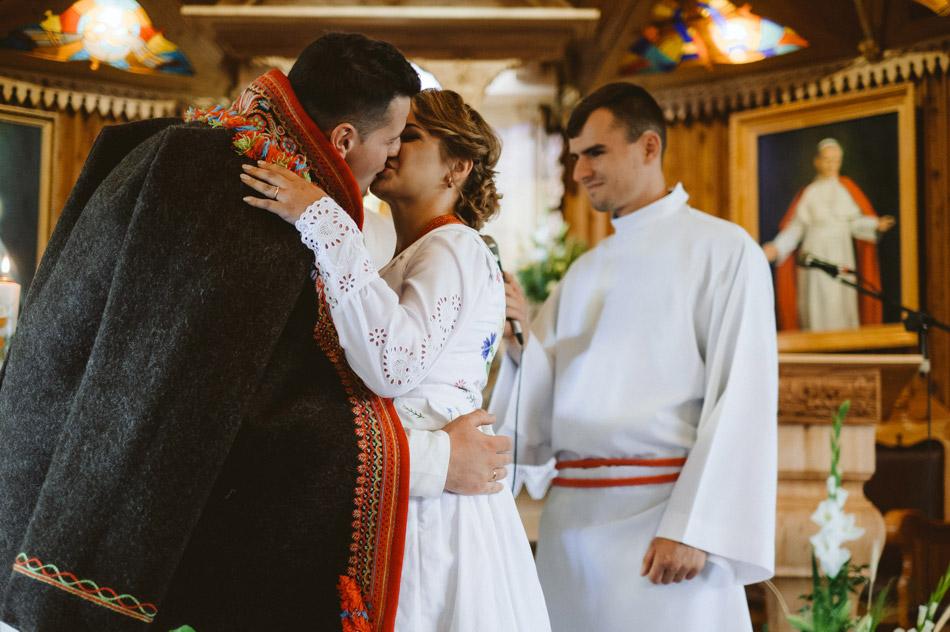 pocałunek pary młodej w kościele po przysiędze ślubnej