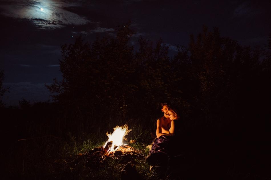 para siedząca przy ognisku podczas pełni księżyca